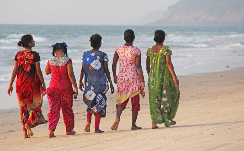 Índia, GOA, o 22 de janeiro de 2018 Um grupo de mulheres indianas em saris brilhantes e coloridos vai ao longo do litoral ou da p foto de stock