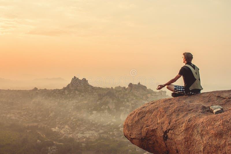 Índia, Hampi - 22 de dezembro de 2015: Um homem está praticando a ioga na parte superior do penhasco durante o alvorecer fotografia de stock royalty free