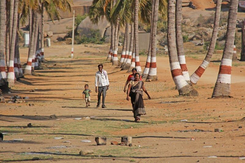 Índia, Hampi, o 2 de fevereiro de 2018 Crianças, homens e mulheres em uma caminhada do sari em um bosque da palma Povos de India fotografia de stock royalty free