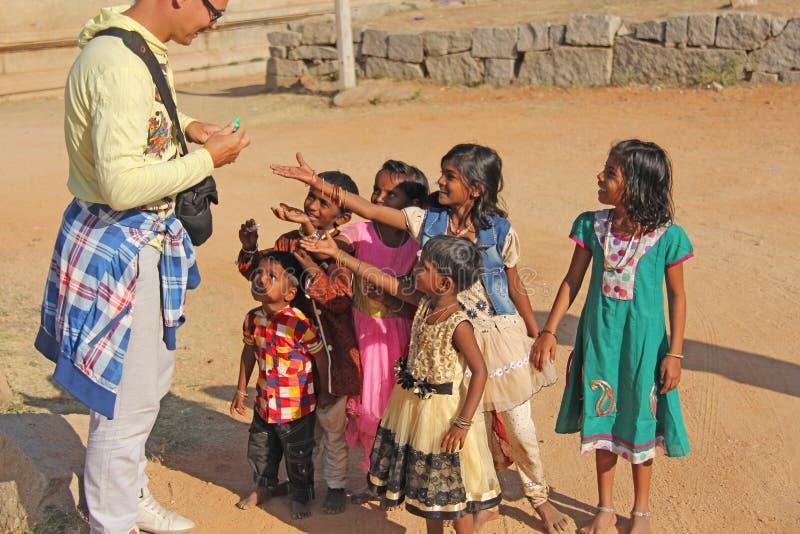 Índia, Hampi, o 2 de fevereiro de 2018 Um homem europeu calvo e alegre dá presentes às crianças indianas As crianças alegres são  foto de stock royalty free