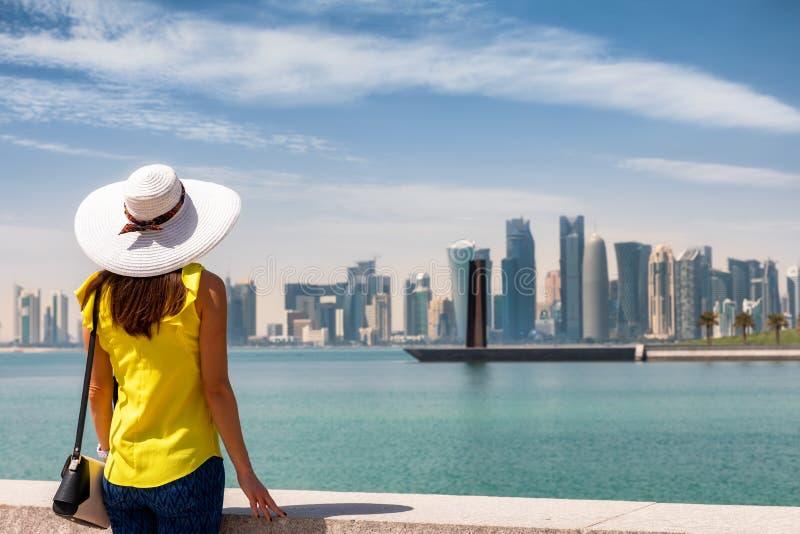 Τraveler tycker om den turist- kvinnan sikten till den stads- horisonten av Doha, Qatar royaltyfri fotografi