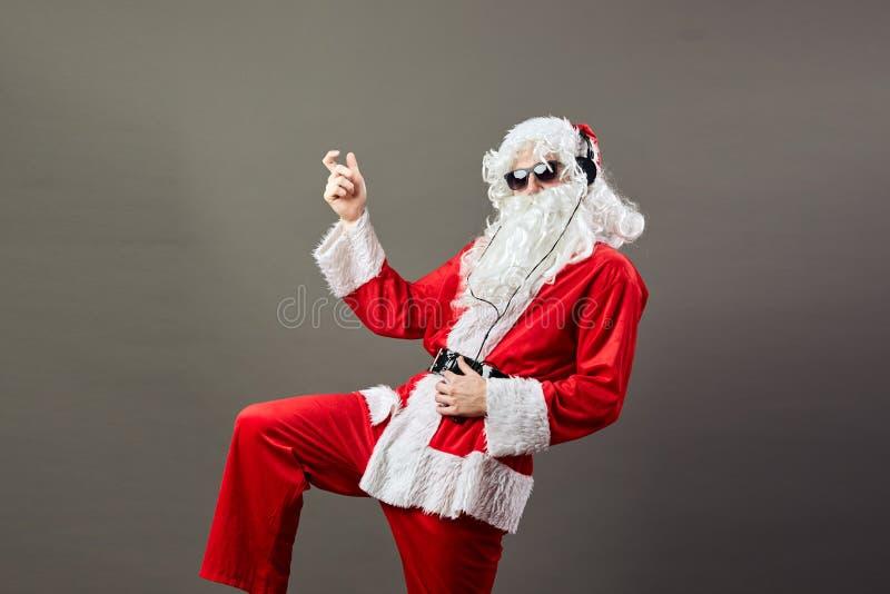 Άγιος Βασίλης με μια μακριά άσπρη γενειάδα στα γυαλιά ηλίου και τα ακουστικά χορεύει όπως ένα αστέρι ύφους βράχου στο γκρίζο υπόβ στοκ φωτογραφίες