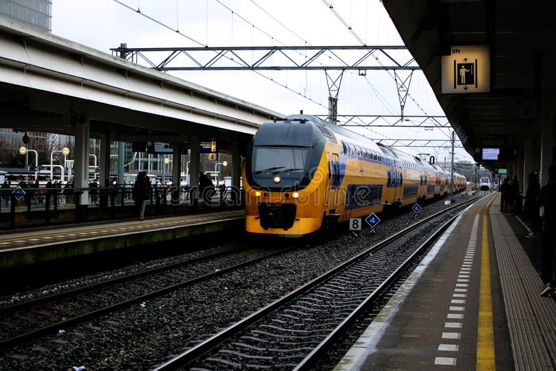 Άμστερνταμ, οι Κάτω Χώρες, στις 7 Μαρτίου 2019: Ένα κίτρινο τραίνο ή intercity από το NS που φθάνει στην πλατφόρμα στοκ φωτογραφία