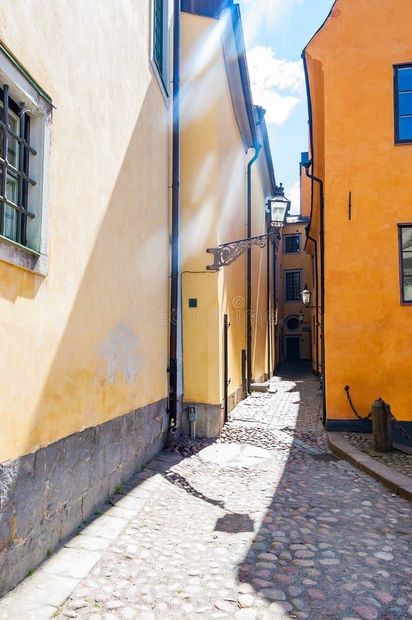 Άνετη στενή οδός με τις κίτρινες πορτοκαλιές προσόψεις κτηρίων στην παλαιά πόλη της Στοκχόλμης στοκ εικόνες