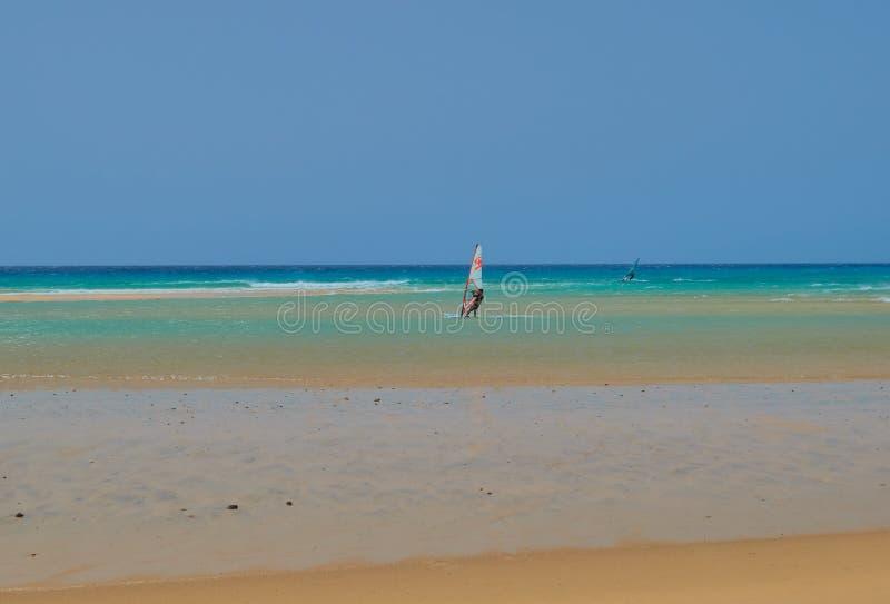 Άνθρωποι που μαθαίνουν να κάνει σερφ σε μια παραλία με τα κύματα και το τυρκουάζ νερό σε Fuerteventura στοκ φωτογραφία