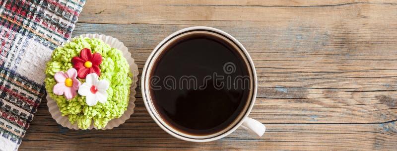 Άνοιξη λουλουδιών cupcake με το καυτό φλυτζάνι καφέ στον ξύλινο πίνακα στοκ εικόνες