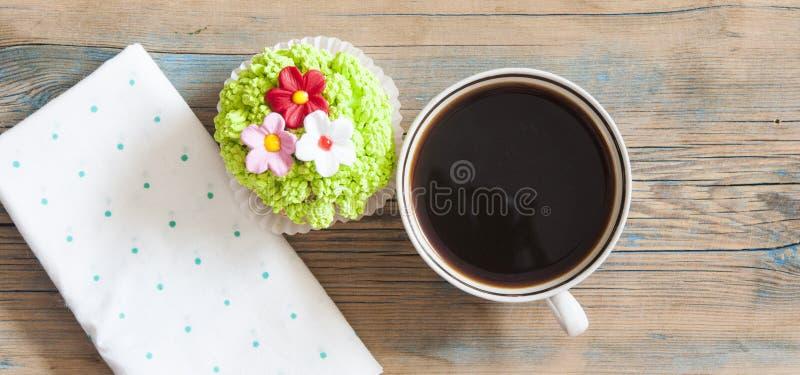 Άνοιξη λουλουδιών cupcake με το καυτό φλυτζάνι καφέ στον ξύλινο πίνακα στοκ φωτογραφία
