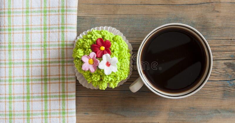 Άνοιξη λουλουδιών cupcake με το καυτό φλυτζάνι καφέ στον ξύλινο πίνακα στοκ εικόνα με δικαίωμα ελεύθερης χρήσης