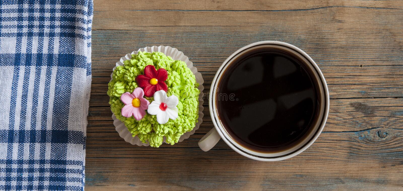 Άνοιξη λουλουδιών cupcake με το καυτό φλυτζάνι καφέ στον ξύλινο πίνακα στοκ φωτογραφία με δικαίωμα ελεύθερης χρήσης