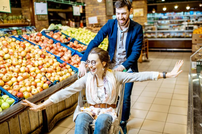 Άνδρας και γυναίκα που έχουν τη διασκέδαση κατά τη διάρκεια των αγορών στην υπεραγορά στοκ εικόνα