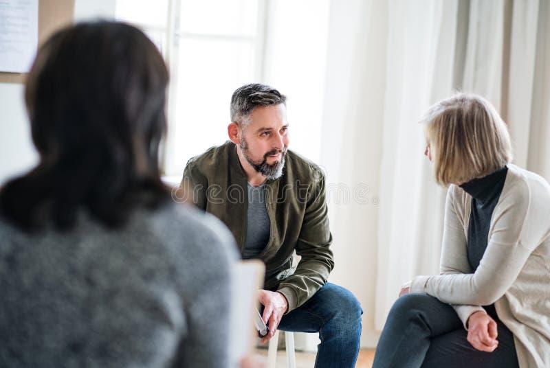 Άνδρας και γυναίκες που κάθονται σε έναν κύκλο κατά τη διάρκεια της θεραπείας ομάδας, ομιλία στοκ εικόνες με δικαίωμα ελεύθερης χρήσης