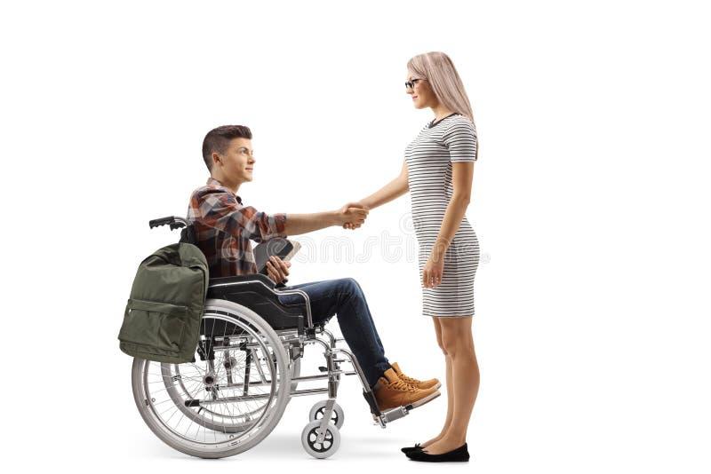 Άνδρας σπουδαστής στα χέρια ενός αναπηρικών καρεκλών τινάγματος με μια νέα γυναίκα στοκ εικόνες με δικαίωμα ελεύθερης χρήσης
