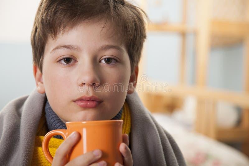 Άρρωστο αγόρι με ένα φλυτζάνι του τσαγιού στο σπίτι στοκ εικόνες