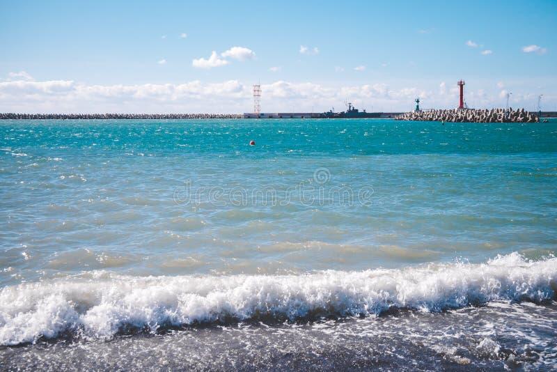 Άσπρα κύματα, τυρκουάζ θάλασσα, φωτεινός μπλε ουρανός, κόκκινος φάρος στοκ εικόνες