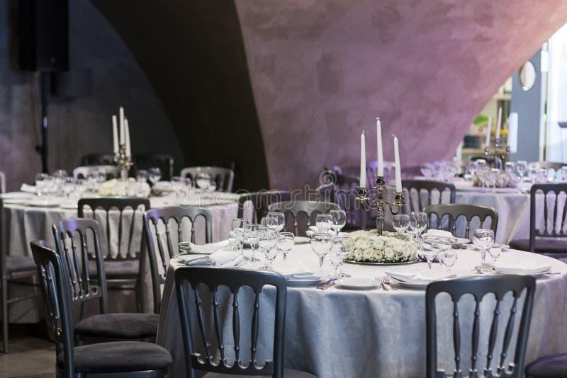 Άσπρες floral ρυθμίσεις με τη στάση πολυελαίων στον πίνακα στο εστιατόριο στοκ φωτογραφία