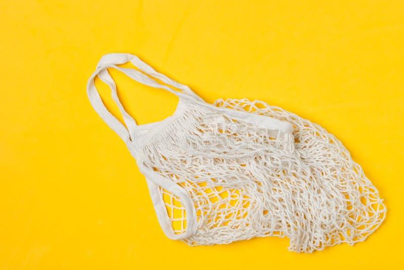 Άσπρη βαμβακιού τσάντα αγορών πλέγματος επαναχρησιμοποιήσιμη, κίτρινο υπόβαθρο, τοπ άποψη - ανακύκλωση, βιώσιμος τρόπος ζωής, μηά στοκ εικόνες