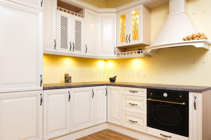 Άσπρη κενή κουζίνα με τα ελαφριά άσπρα έπιπλα - θερμά φω'τα και ωραία διακοσμημένο ξύλο στοκ φωτογραφία