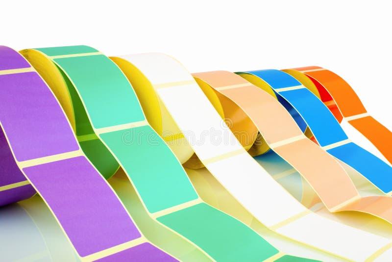 Άσπροι και χρωματισμένοι ρόλοι ετικετών που απομονώνονται στο άσπρο υπόβαθρο με την αντανάκλαση σκιών Εξέλικτρα χρώματος των ετικ στοκ εικόνες