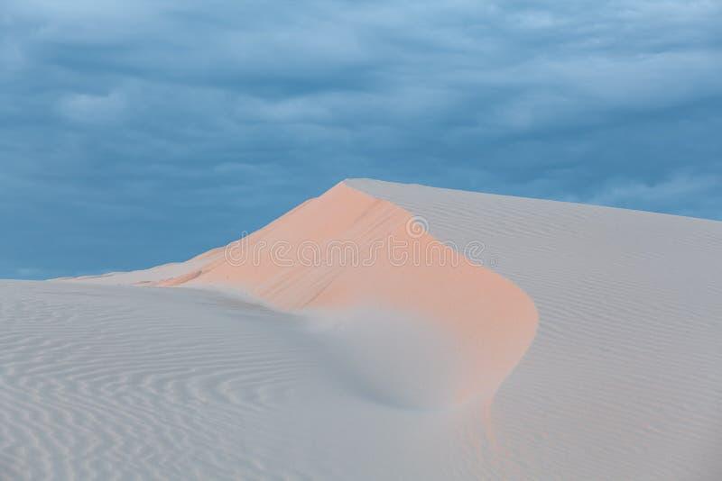 Άσπρος αμμόλοφος άμμου κάτω από τους νεφελώδεις ουρανούς ηλιοβασιλέματος απεικόνιση αποθεμάτων