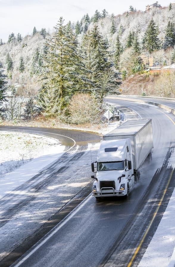 Άσπρο μεγάλο ημι φορτηγό εγκαταστάσεων γεώτρησης που μεταφέρει το φορτίο στην ημι οδήγηση ρυμουλκών στο τύλιγμα του δρόμου χειμερ στοκ φωτογραφία