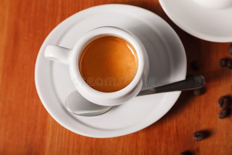 Άσπρο φλυτζάνι καφέ με τον εύγευστο αφρό, τοπ άποψη κινηματογραφήσεων σε πρώτο πλάνο στο ξύλινο υπόβαθρο Έννοια του διαλείμματος  στοκ φωτογραφία