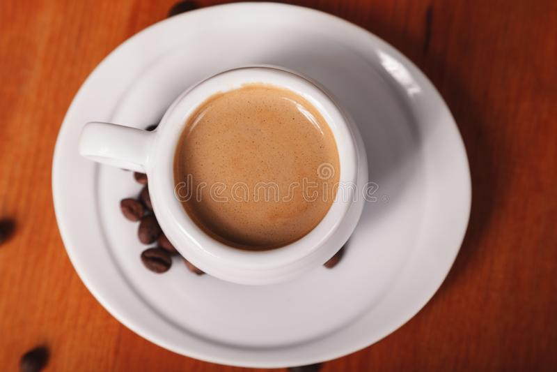 Άσπρο φλυτζάνι καφέ με τον παχύ αφρό γάλακτος, τοπ άποψη κινηματογραφήσεων σε πρώτο πλάνο στον ξύλινο πίνακα Έννοια του διαλείμμα στοκ εικόνα