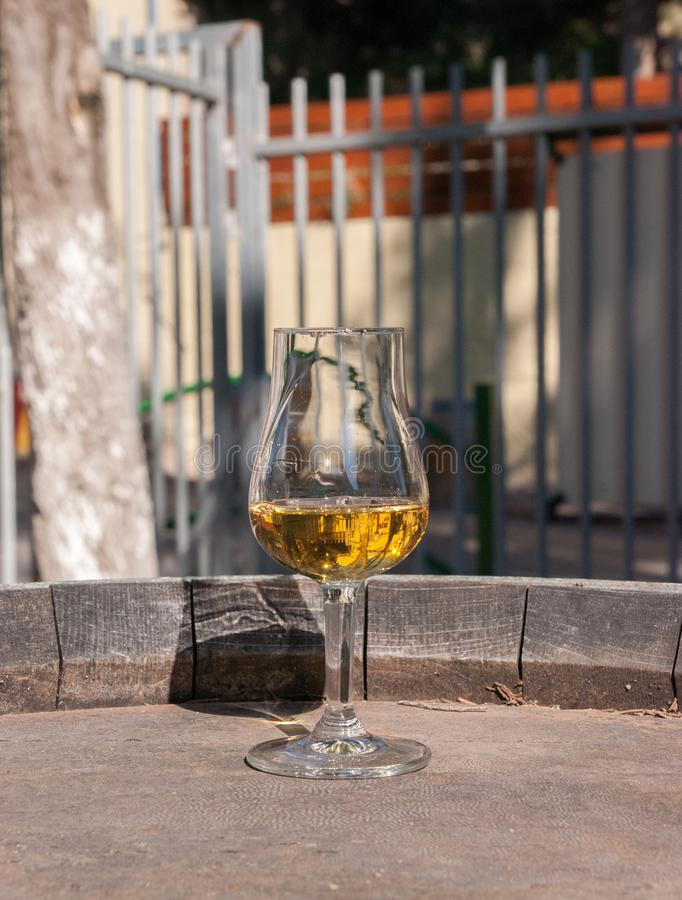 Άσπρο semi-sweet κρασί σε ένα γυαλί, στο παλαιό εκλεκτής ποιότητας βαρέλι στοκ εικόνες