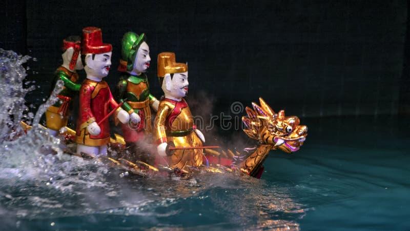 Άτομα που οδηγούν τις μαριονέτες ενός δράκων νερού στο μακρύ θέατρο μαριονετών νερού Thang, Ανόι, Βιετνάμ στοκ εικόνα