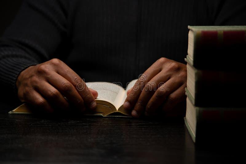 Άτομο αφροαμερικάνων που μελετά στο γραφείο με τα βιβλία στοκ εικόνα με δικαίωμα ελεύθερης χρήσης