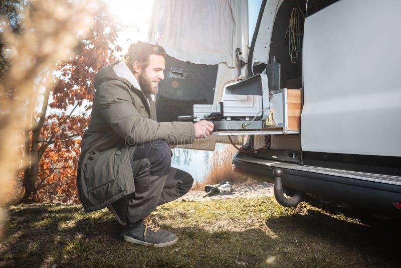 Άτομο μπροστά από ένα φορτηγό που χρησιμοποιεί μια κατασκευή στη σόμπα στρατοπέδευσης στοκ εικόνες με δικαίωμα ελεύθερης χρήσης
