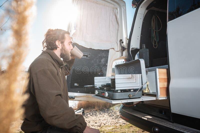 Άτομο δίπλα στο φορτηγό τροχόσπιτών του που έχει ένα φλιτζάνι του καφέ στοκ εικόνες