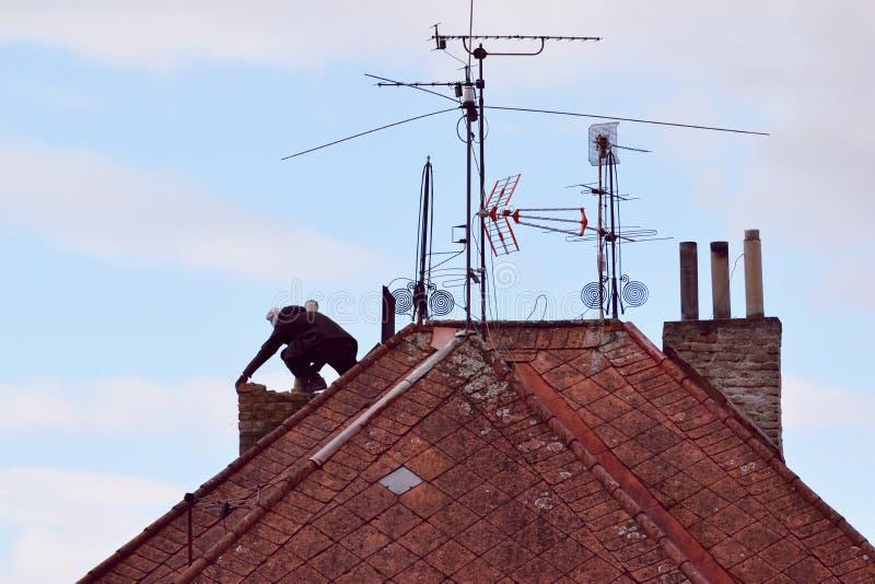Άτομο που ανακαινίζει μια παλαιά καπνοδόχο στη στέγη στοκ φωτογραφίες