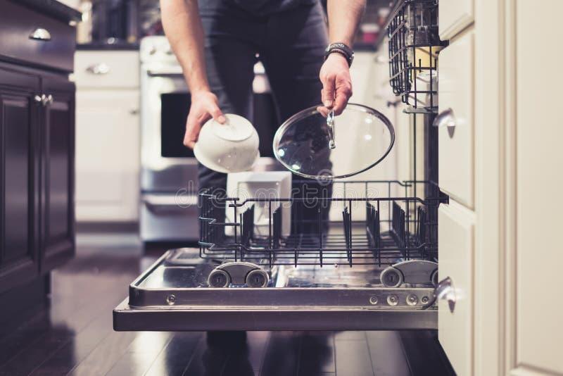 Άτομο που κάνει τα πιάτα που καθαρίζουν στις οικιακές μικροδουλειές κουζινών στοκ εικόνα