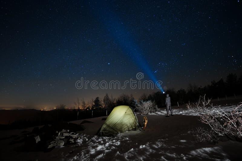 Άτομο που δείχνει τον μπλε φακό τον έναστρο ουρανό στοκ φωτογραφία