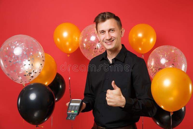 Άτομο που παρουσιάζει αντίχειρα επάνω στη λαβή το ασύρματο σύγχρονο τερματικό πληρωμής τραπεζών στη διαδικασία αποκτά τη μαύρη κά στοκ φωτογραφίες