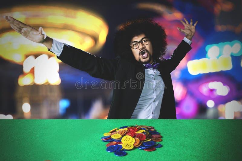 Άτομο Afro που γιορτάζει τη νίκη του στη χαρτοπαικτική λέσχη στοκ φωτογραφίες με δικαίωμα ελεύθερης χρήσης
