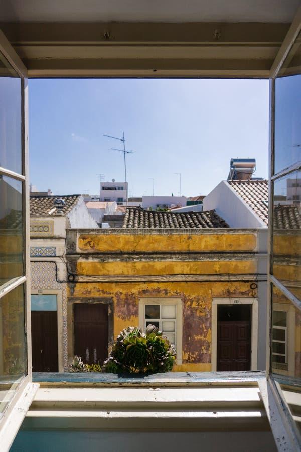 Άποψη οδών Faro Πορτογαλία παραθύρων ξενοδοχείων με τις εγκαταστάσεις στο παράθυρο στοκ φωτογραφία