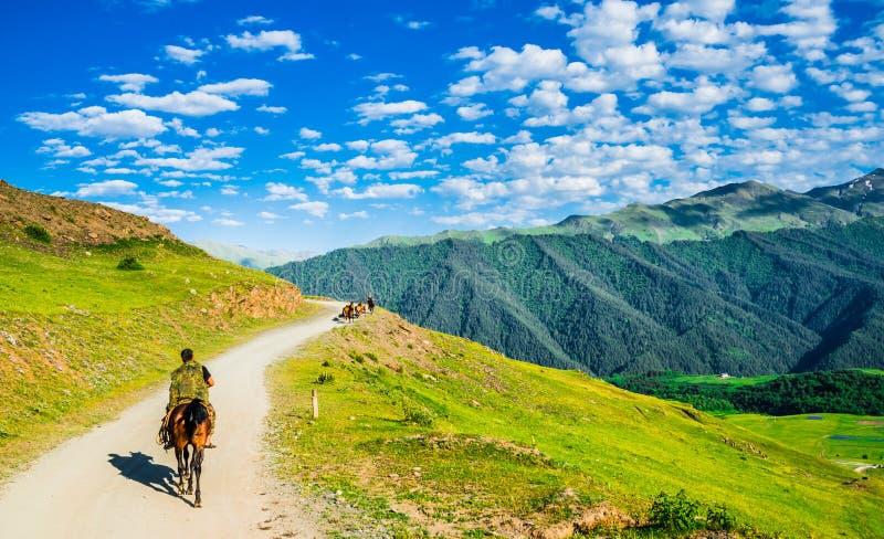 Άποψη σχετικά με τα πρόσωπα που κάνουν την οδοιπορία αλόγων στα βουνά Tusheti, Γεωργία στοκ φωτογραφία με δικαίωμα ελεύθερης χρήσης