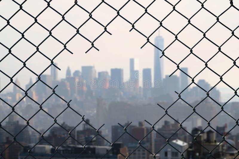 Άποψη σχετικά με την πόλη της Νέας Υόρκης μέσω της τρύπας του φράκτη καλωδίων πλέγματος χάλυβα Έννοια στοκ φωτογραφία με δικαίωμα ελεύθερης χρήσης