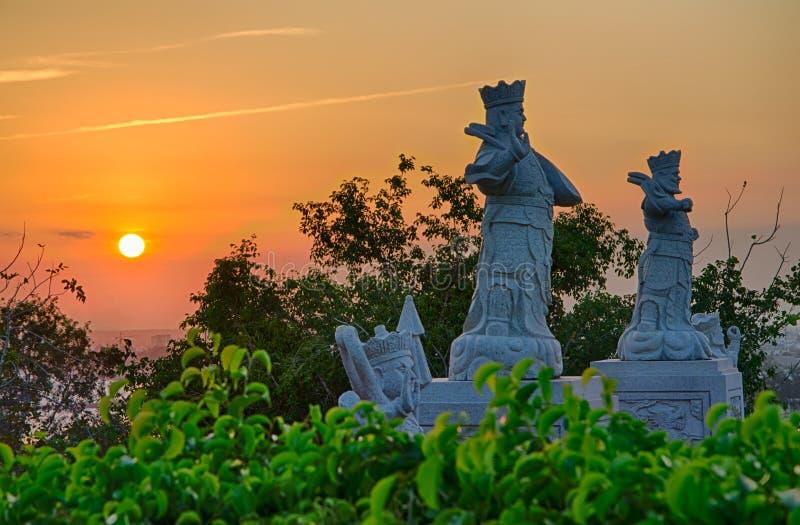 Άποψη του ηλιοβασιλέματος από έναν βουδιστικό ναό στο βουνό χρυσός ουρανός Μαρμάρινα αγάλματα των πολεμιστών στη μέση των δέντρων στοκ εικόνες