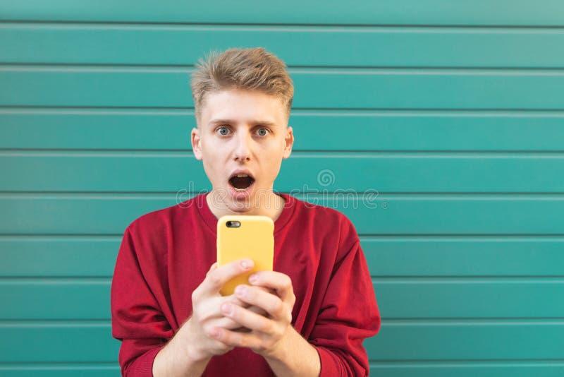 Έκπληκτος νεαρός άνδρας με ένα smartphone στα χέρια του που εξετάζουν τη κάμερα ενάντια στο σκηνικό ενός τυρκουάζ τοίχου στοκ εικόνες