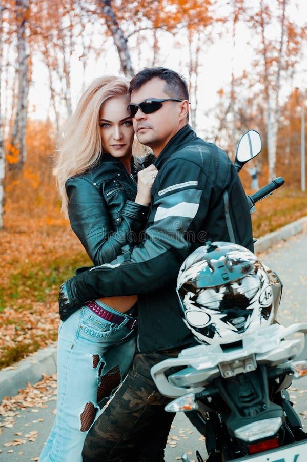 Ένας ελκυστικός τύπος και μια νέα γυναίκα σε μια μαύρη εξάρτηση δέρματος με μια μοτοσικλέτα στοκ φωτογραφία με δικαίωμα ελεύθερης χρήσης