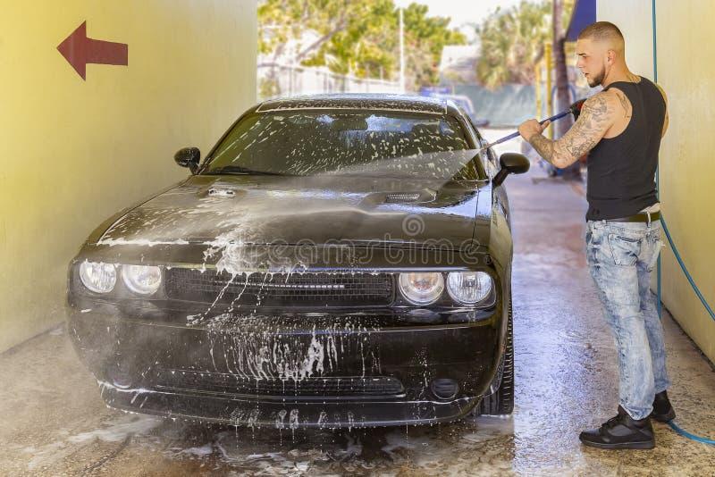 Ένας εργαζόμενος ξεπλένει αργά το μέτωπο ενός μαύρου αυτοκινήτου στο πλύσιμο αυτοκινήτων στοκ εικόνες με δικαίωμα ελεύθερης χρήσης