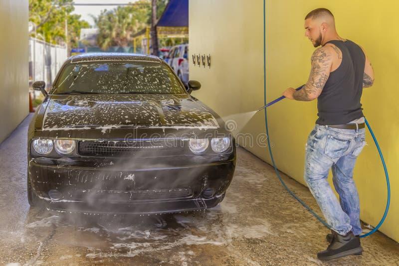 Ένας εργαζόμενος ξεπλένει από ένα μαύρο αυτοκίνητο στο πλύσιμο αυτοκινήτων στοκ εικόνες με δικαίωμα ελεύθερης χρήσης