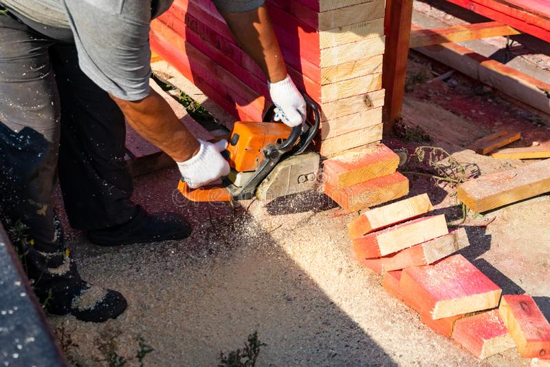 Ένας εργαζόμενος πριονίζει από έναν ξύλινο πίνακα αλυσιδοπριόνων μπροστινά Windows σπιτιών γκαράζ πορτών λεπτομέρειας κατασκευής στοκ φωτογραφίες με δικαίωμα ελεύθερης χρήσης