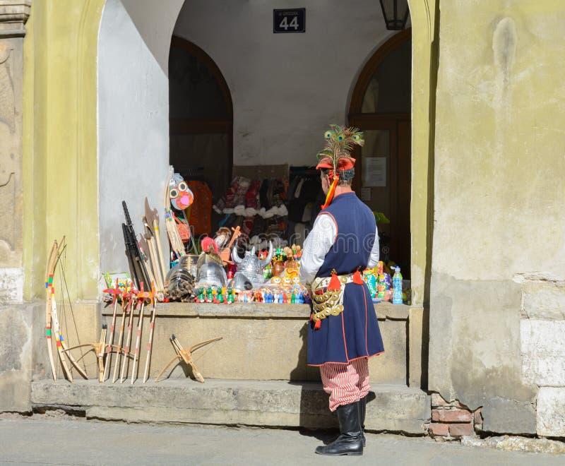 Ένας κομψός τουρίστας επιλέγει τα δώρα στο μετρητή ενός καταστήματος αναμνηστικών στοκ εικόνα