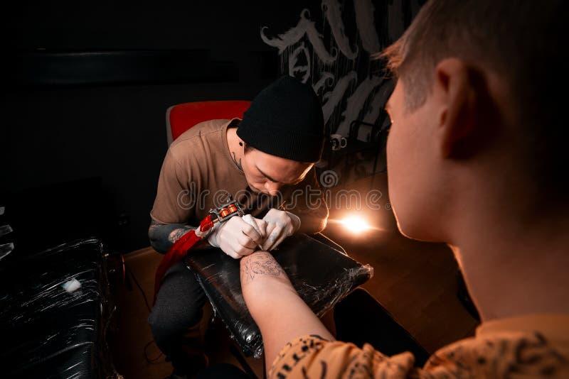 Ένας κύριος ατόμων γεμίζει μια δερματοστιξία σε έναν νεαρό άνδρα Αίθουσα δερματοστιξιών Στρέθιμο της προσοχής στο δέρμα στοκ φωτογραφία