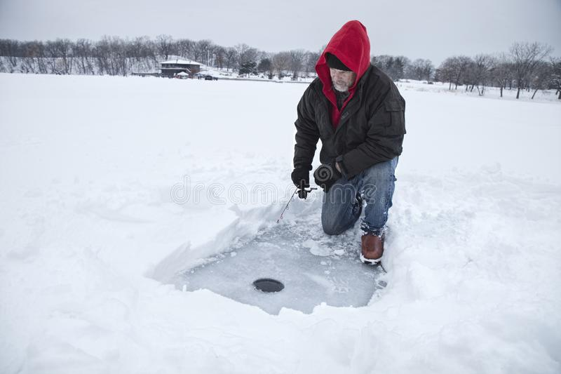 Ένας μέσος ηλικίας πάγος ατόμων που αλιεύει σε μια λίμνη σε Μινεσότα κατά τη διάρκεια του χειμώνα στοκ φωτογραφίες