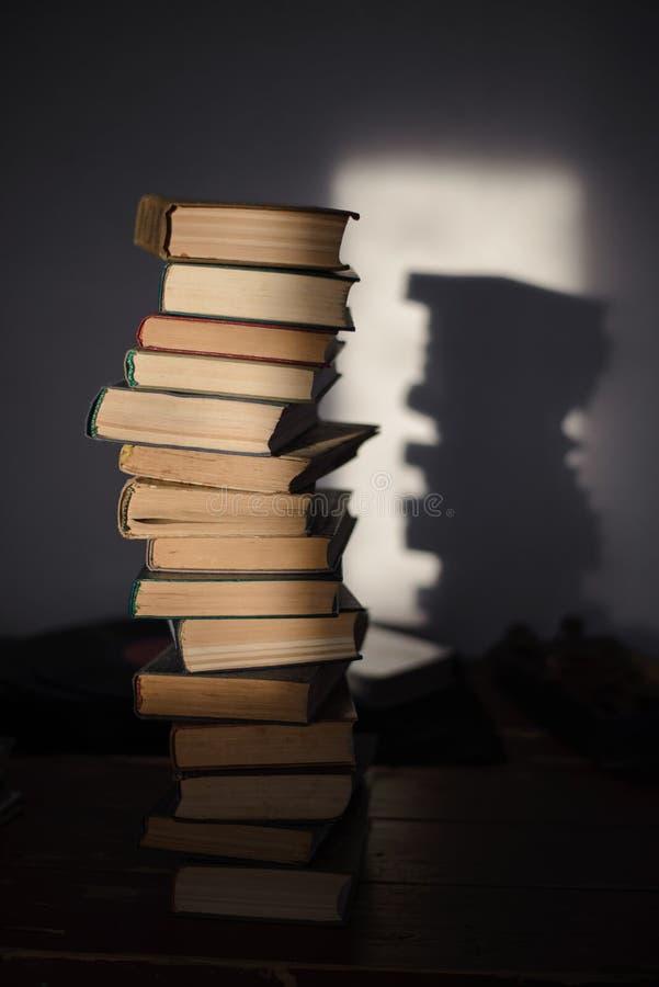Ένας μεγάλος σωρός των παλαιών βιβλίων στον πίνακα αναμμένο λαμπρά από τον ήλιο στοκ εικόνα