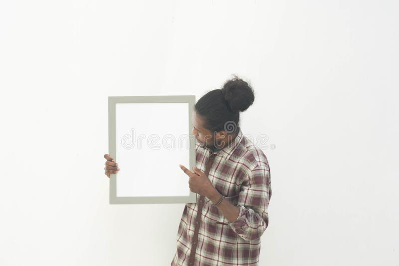 Ένας νέος μαύρος που κρατά τον κενό λευκό πίνακα με το απομονωμένο υπόβαθρο στο λευκό στοκ φωτογραφία με δικαίωμα ελεύθερης χρήσης
